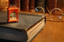 8089551-vintage-still-life-small-wooden-clock-standing-on-old-book-on-background-with-books-and-spectacles